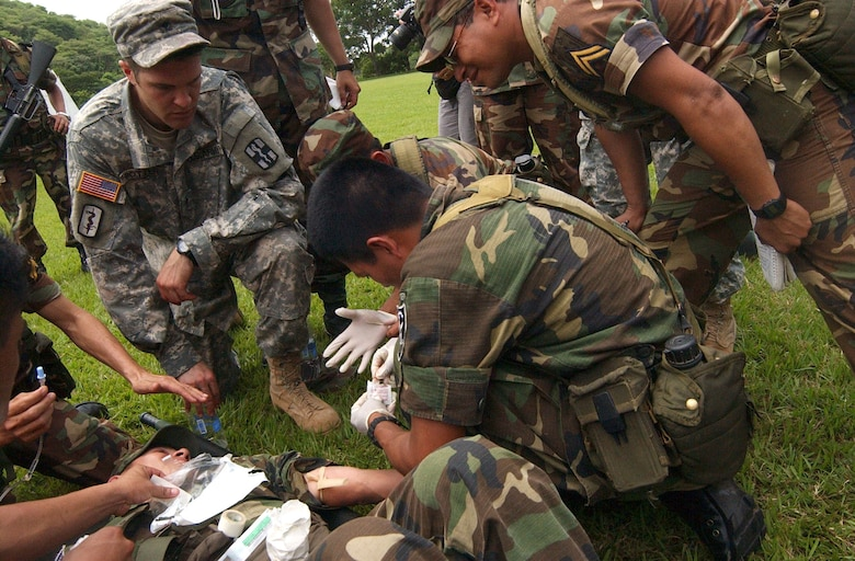 Army Specialist Jonathan Potter, who provided medical instruction during the week-long training with the El Salvadorian military, watches as a student prepares to administer an intravenous needle into a wounded soldier. Air Force photo by Senior Airman Shaun Emery.