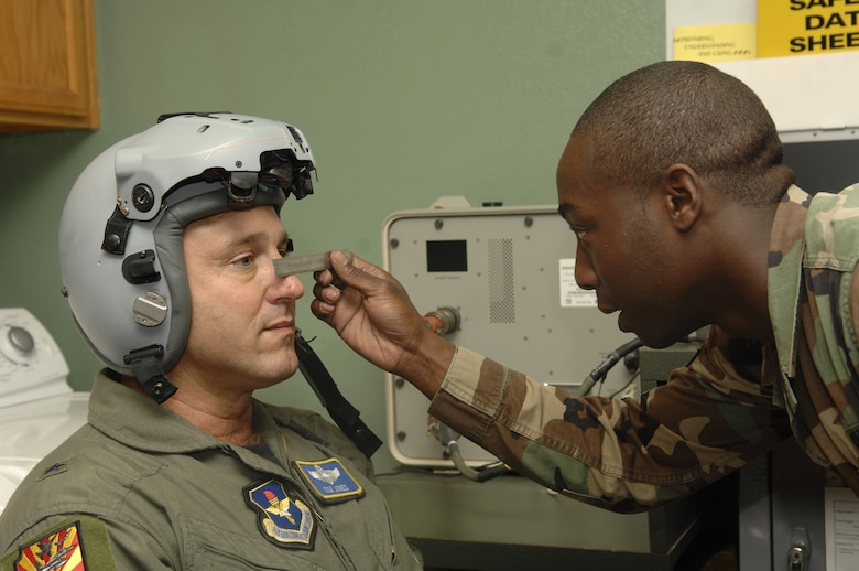 LEFT: Brig. Gen. Tom Jones, 56th Fighter Wing commander, is fitted for the new joint helmet mounted cueing system by Senior Airman Willis Austin, 310th Fighter Squadron Aircrew Life Support journeyman.  Each helmet costs approximately $110,000.  Photo by Master Sgt. William Gomez.