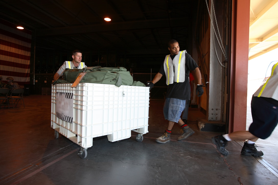 Deployment Operations Division personnel transport cargo during the Phase I exercise July 19. They handle various items used for deployments such as mobility bags, insect repellant, weapons and individual body armor. (Photo by Jet Fabara)