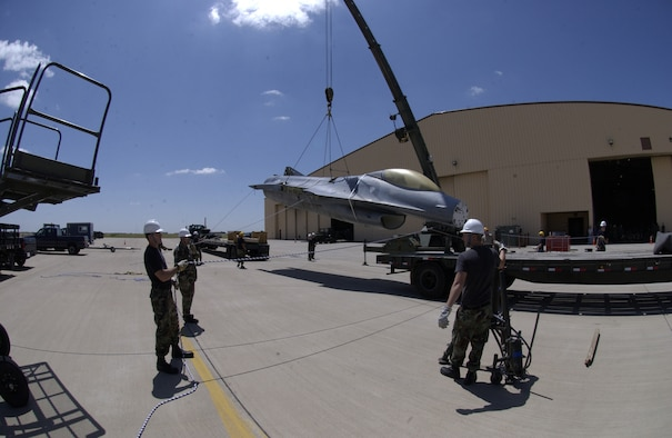 After lifting the fuselage of an F-16 off a trailer bed, Airmen steady it to be moved onto the bed of the truck in the background. The F-16, which was originally from Sheppard Air Force Base, Texas, will become a static display at the air park near the main gate. (U.S. Air Force photo by Airman Elliott Sprehe)