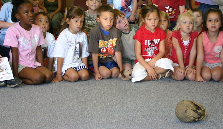 """Children from around base wait for an armadillo to come out of its shell at the library here June 19. The Albuquerque Zoo brought out reptiles, amphibians, birds and mammals as part of the """"Catch the Beat"""" program at the library. (U.S. Air Force photo by Airman Elliott Sprehe)"""
