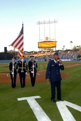 Lt. Col. Ivan Thompson, SMC,  sings the National Anthem and a Los Angeles Air Force Base Honor guard posts the colors at a Los Angeles Dodger game, July 20. The annual Dodger Day event is sponsored by the City of El Segundo. (Photo by Paul Testerman)