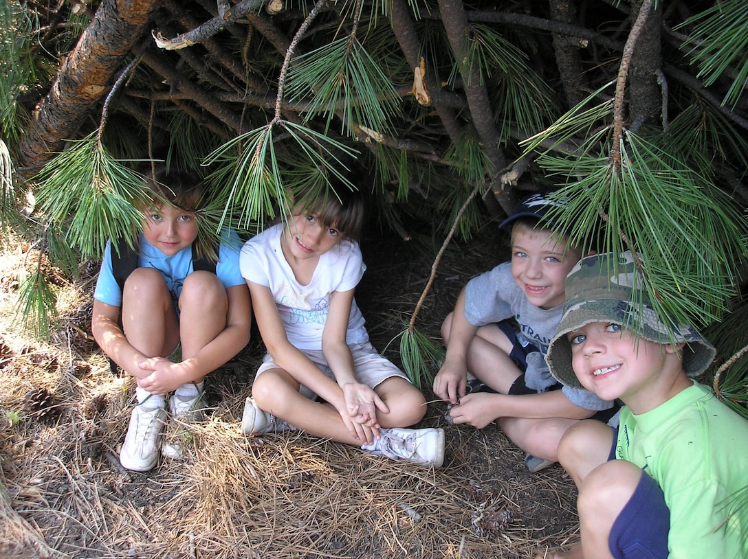 SPOKANE, Wash. – From left, Makyla Carney, Katherine Schmoldt, Issac Detiege and Matthew Lacey sit in a shelter built by instructors from the Survival, Evasion, Resistance and Escape School at Fairchild Air Force Base, Wash. The children attended the Blue Green Summer Youth Camp here July 16 - 20, where they learned a bit about deployed environments and learned coping strategies for separation stresses. The camp is a joint-service camp designed specifically for children with deployed parents. This year, all Department of Defense services were represented through the young campers. (U.S. Air Force photo/ Melissa Still)