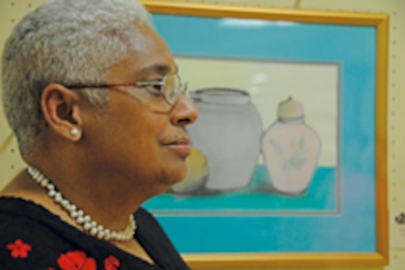 "Artist Cynthia Ferguson, of the Wright Patterson Air Force Base Officers Wives Club, displays her painting entitled ""Tranquility"" July 18 at an exhibit hosted by the club in the Dayton Public Library downtown branch. (Air Force photo/Christy Webb)"