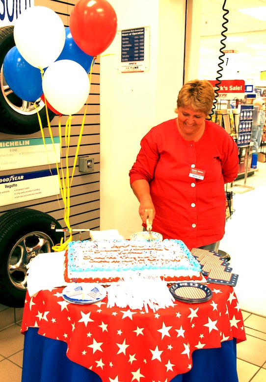 WHITEMAN AIR FORCE BASE, Mo. -- Becky Stover, Whiteman Base Exchange manager, cuts the Army and Air Force Exchange Services' 112th anniversary cake at the Whiteman BX July 25. (U.S. Air Force photo/Airman 1st Class Stephen Linch)