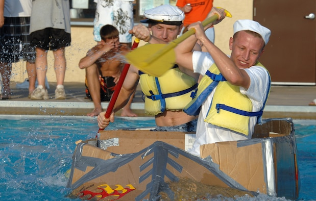 WHITEMAN AIR FORCE BASE, Mo. -- Senior Airman Robert Heidenreich (front) and Staff Sgt. Joshua Hollingshead, both from the 509th Maintenance Squadron, race across the base pool in the S.S. Minnom to a 1st place finish with a time of 14 seconds during the 509th Services Squadron's Build-a-Boat contest July 20. More than 10 teams had 40 minutes to construct race-worthy boats of cardboard and duct tape. (U.S. Air Force photo/Airman 1st Class Stephen Linch)