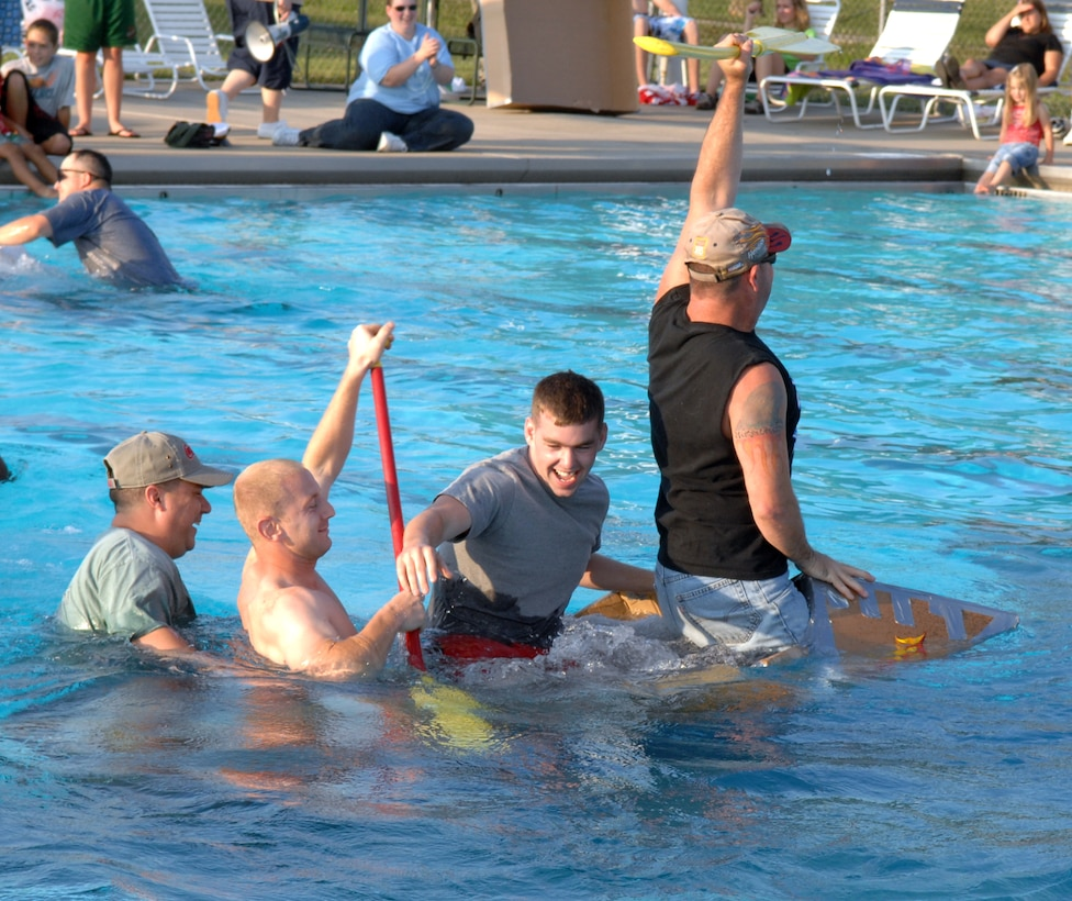 "WHITEMAN AIR FORCE BASE, Mo. -- The crew of the S.S. Minnom go down with their cardboard ship during the ""best sinking"" portion of the Build-a-Boat contest at the base pool July 20. The base pool is open Tuesday through Friday from 1:15 to 6:00 p.m. and Saturday and Sunday noon to 6 p.m. (U.S. Air Force photo/Airman 1st Class Stephen Linch)"