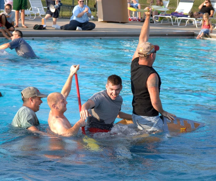 """WHITEMAN AIR FORCE BASE, Mo. -- The crew of the S.S. Minnom go down with their cardboard ship during the """"best sinking"""" portion of the Build-a-Boat contest at the base pool July 20. The base pool is open Tuesday through Friday from 1:15 to 6:00 p.m. and Saturday and Sunday noon to 6 p.m. (U.S. Air Force photo/Airman 1st Class Stephen Linch)"""