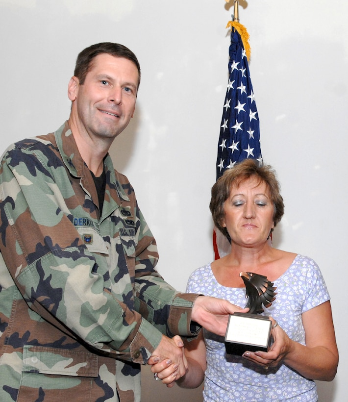 LAJES FIELD, Azores, Portugal – Filomena Silva, 65th Medical Group, is congratulated by Col. Jeff Derrick, 65th Air Base Wing vice commander, on being selected as the Category II, Portuguese Civilian of the Quarter for April to June 2007 during the Quarterly Awards Ceremony in the Top of the Rock Club here July 18, 2007. (U.S. Air Force photo by Guido Melo)