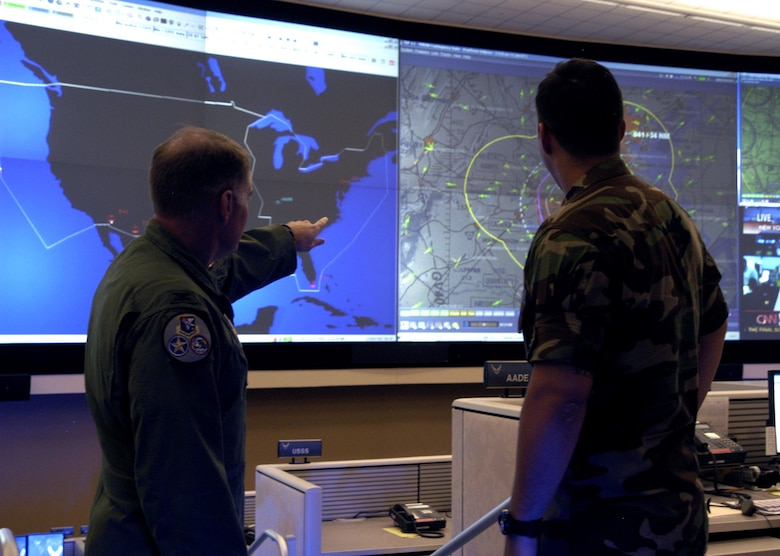 Col. Kriner shows 2nd Lt. Andrew Scott, 601st AOC, air tracks over the National Capital Region. The new AOC is equipped with a $3.5 million data wall to better monitor air traffic across the nation.