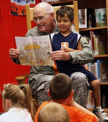 Five-year-old Jovannie Arroyo helps Maj. Gen. Lorren Reno, Oklahoma City Air Logistics Center commander, read to children during the Tinker Library's story time July 19. (Air Force photo by Becky Pillifant)