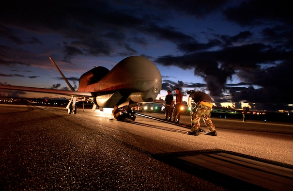 A flightline ground crew secures a RQ-4 Global Hawk Unmanned Aerial Vehicle for towing to a secure hangar July 19. The Global Hawk is from the 9th Reconnaissance Wing at Beale Air Force Base, Calif. (U.S. Air Force photo/Senior Airman Miranda Moorer)