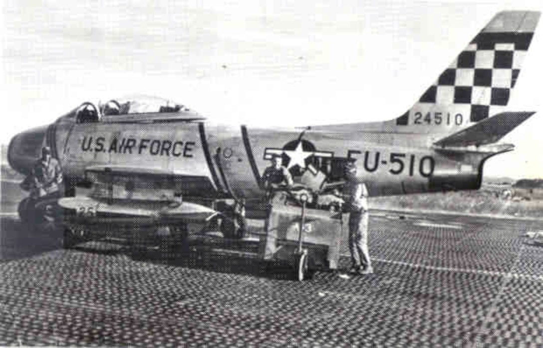 """Ground crews prepare an F-86 Sabre with its 51st Fighter Interceptor  Wing  """"Checkertail"""" for flight during the Korean War.  (Courtesy photo)"""