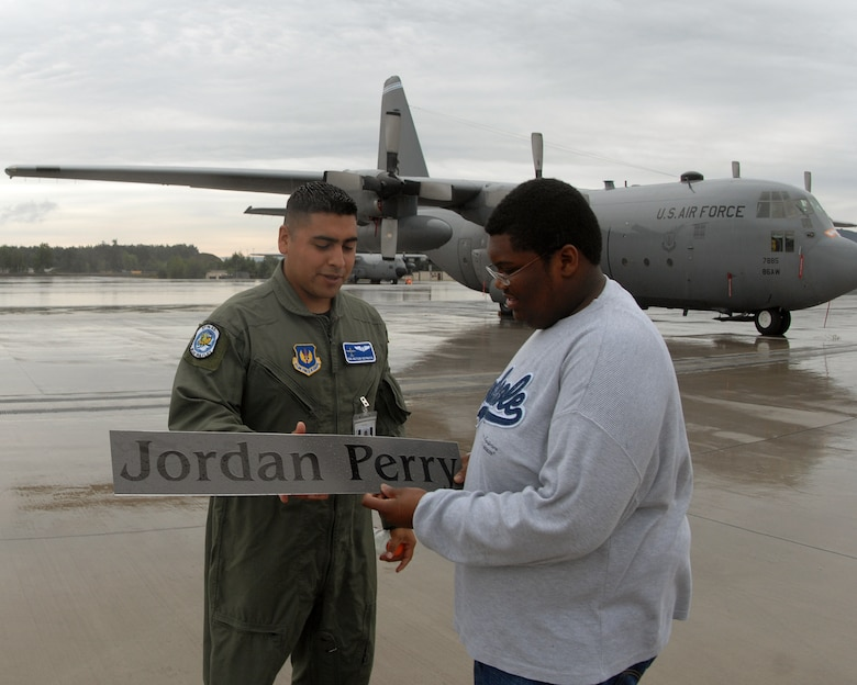 Senior Airman Victor Rynosa, 37th Airlift Squadron crew chief, hands Jordan Perry a sign with his name on it. The sign had been placed on the side of a C-130 to welcome Jordan for his tour of Ramstein Air Base July 21, 2007. Jordan, who recenlty beat cancer, had the wish to visit Ramstein Air Base. Jordan's dad, Lester Perry, a retired first sergeant, was stationed in Germany in the early 90's and was happy to see his son be able to live out his dream. (U.S. Air Force Photo/Airman 1st Class Kenny Holston)