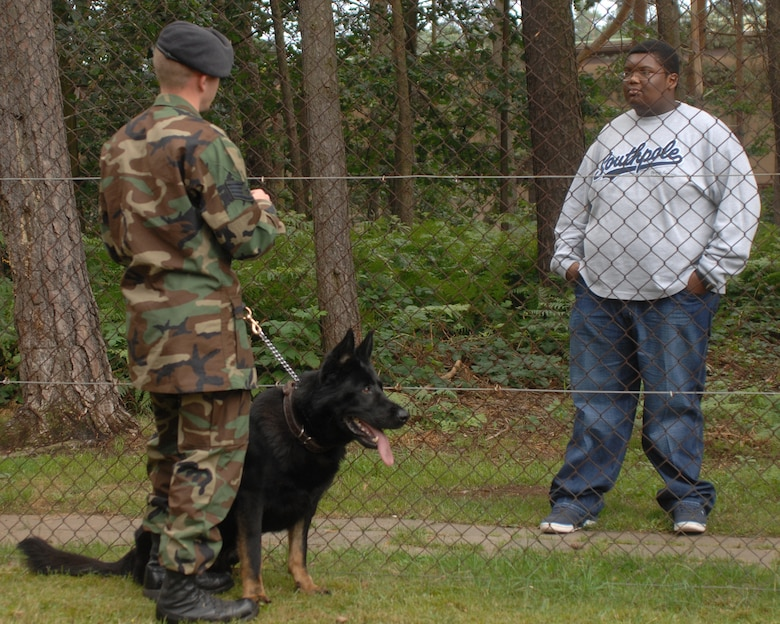 Staff Sgt. Jonathan Beaver, 435th Security Forces Squadron dog handler, explains to Jordan Perry how police dogs are used by security forces every day, before showing Jordan a demonstration July 21, 2007 at Ramstein Air Base Germany. Jordan, who recently beat cancer, had a wish to visit Ramstein Air Base. Jordan's dad, Lester Perry, a retired first sergeant, was stationed in Germany in the early 90's.   (U.S. Air Force photo/Airman 1st Class Kenny Holston)
