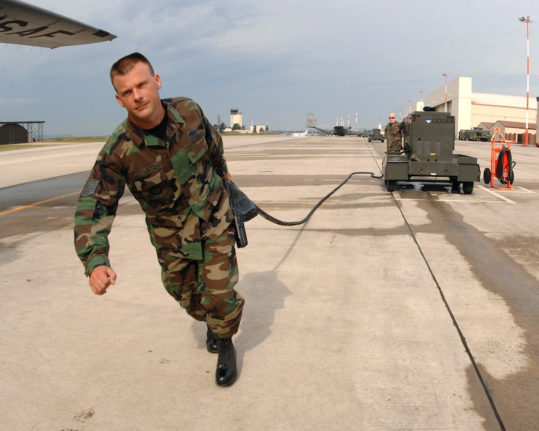 Tech. Sgt. Laurence Littleton, 86th Maintenance Operations Squadron, pulls an aerospace and ground equipment power cord toward a parked C-130 to give the plain external power while it's parked on the Ramstein flight line July 19, 2007 at Ramstein Air Base Germany. AGE equipment is used to give parked aircraft external power so the aircraft doesn't have to continue to run after its parked, which in turn saves the Air Force fuel and money and helps ensure mission success. (U.S. Air Force Photo/A1C Kenny Holston)