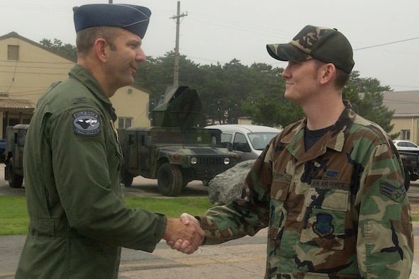"""KUNSAN AIR BASE, Republic of Korea -- Col. Creig """"Wolf 2"""" Rice, 8th Fighter Wing vice commander, congratulates Senior Airman Jake Capps of the 8th Maintenance Squadron, July 20. Airman Capps was the Wolf Pack's Pride of the Pack for the week of  July 23. (U.S. Air Force photo/Senior Airman Giang Nguyen)"""