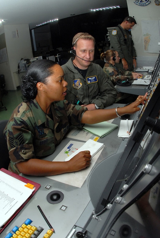 Tech. Sgt. Connie Brent (left) and Maj. Charles Dennison, both with the 623rd Air Control Flight, control ae Large Force Exercise (LFE) by using the Base Air Defense Ground Environment system. Sergeant Brent relays time- sensitive information to Maj. Dennison, the mission crew commander, where he controls the air space by guiding aircraft into different sections according to the mission plan.  U.S. Air Force photo/Staff Sgt. Steven Nabor