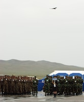FIVE HILLS TRAINING CENTER, Mongolia (Aug. 1, 2007) â?? As if the spirit of Chinghis Khaan himself rode the winds down from heaven, a bird of prey swoops in on the opening ceremony for exercise Khaan Quest 07 held here Aug. 1. Approximately 1,000 multinational service members converged on the training center here for exercise Khaan Quest 07 to increase their peacekeeping abilities. (Official U. S. Marine Corps photo by Sgt. G. S. Thomas)