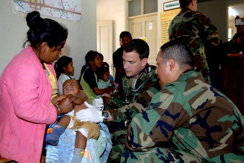 Maj. Scott Shepherd and Senior Airman Felipe Soto treat a 6-month old Bolivian boy who has a fever of 104 degrees during a Medical Readiness Training Exercise in Cobija, Bolivia. The two medics are part of a 30-member medical team in Bolivia treating underserved populations in the country. Major Shephers is assigned to the 152nd Medical Group in Reno, Nev., and Airman Soto is from the 163rd Medical Group. (U.S. Air Force photo)
