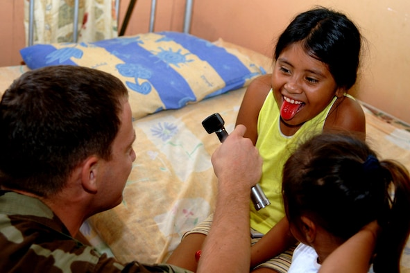 """Maj. Scott Shepherd makes a daring attempt to have a Bolivian girl say """"Ahhhhh"""" during a Medical Readiness Training Exercise in Cobija, Bolivia. The major, assigned to the 152nd Medical Group in Reno, Nev., was part of a 30-member medical team in Bolivia treating underserved populations in the country. (U.S. Air Force photo)"""