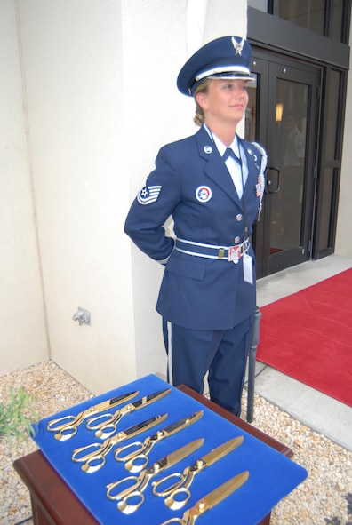 "Honor Guard member Technical Sergeant Tiffany Kellum stands guard over the golden scissors used to cut the ribbon at the grand opening of ""America's AOC""."