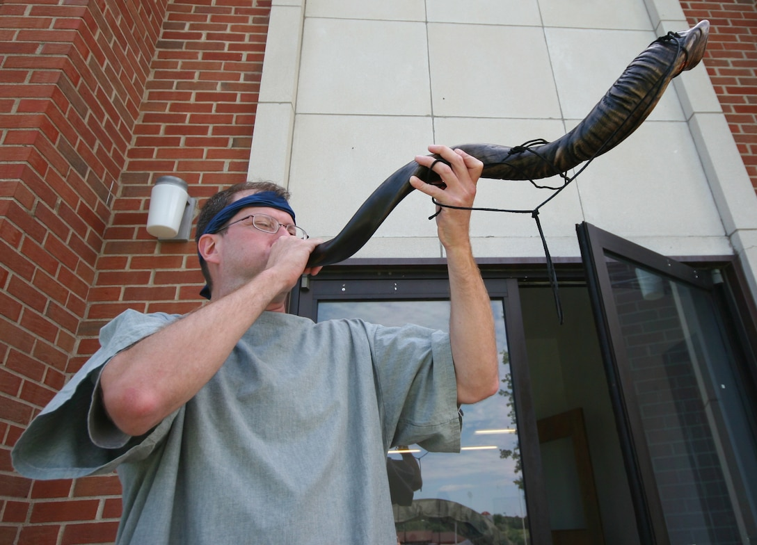 """Chaplain (Capt.) James Pitney, 509th Bomb Wing chapel, uses a shofar, or ram's horn, to call members to lunch during the Whiteman Chapel's Vacation Bible School, """"Marketplace 29 A.D."""" June 1. U.S. Air Force photo/Tech. Sgt. Matt Summers."""
