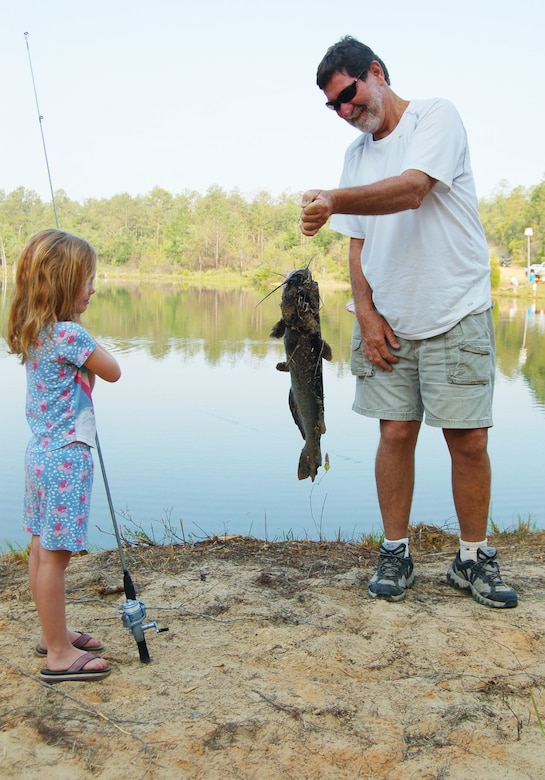 EGLIN AIR FORCE BASE, Fla. -- Rhianna Hamilton keeps a safe distance from her catch as her grandfather Steve Griner showcases her accomplishment at the Eglin Youth Fishing Rodeo May 26-27. The event was held on Prisoner Pond, an approximately five acre lake at the 6th Ranger Training Battallion compound. Members of the U.S. Fish and Wildlife Service stocked the pond with approximately 3,000 channel catfish that were provided by the USFWS Welaka National Fish Hatchery in preparation for the Rodeo event. Additionally, Jackson Guard purchased approximately 1,000 pounds of catfish that was added to the pond before the event. (U.S. Air Force photo by Jerron Barnett)