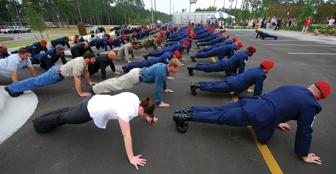 Special tactics Airmen and family members of fallen special tactics warriors join in memorial pushups during the dedication of the Crate Special Tactics Advanced Skills Training Center at Hurlburt Field Wednesday. The center will provide operational training to newly-minted special tactics Airmen.  It is named for Staff Sgt. Casey Crate, a combat controller who lost his life in the crash of an Iraqi air force aircraft in 2005. (U.S. Air Force photo by Chief Master Sgt. Gary Emery)