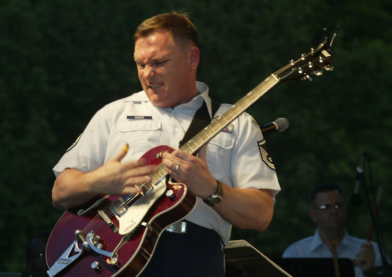 "Master Sgt. James Weber a member of The Heartland of America Band, The Noteables, from Offutt Air Force Base, Neb., performs a guitar solo for the crowd at Stone Mountain, Ga., as a part of a""Salute the Troops"" Memorial Day celebration. (U.S. Air Force photo/Don Peek)"