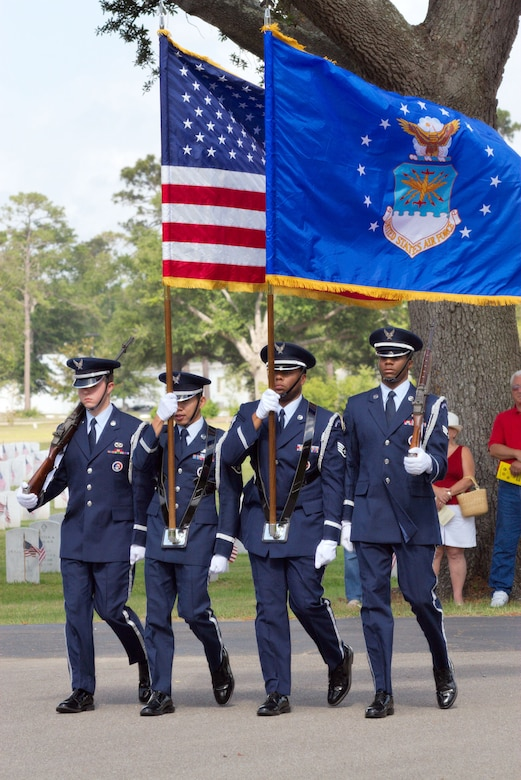 Keesler Honor Guard members A1C Aaron Scott, SSGT Michael De Guzman, SSGT Wade Woods and SrA Marcus Anderson carry the colors on Memorial Day.
