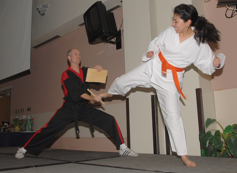 With a precise amount of force and direction, Staff Sgt. Jenny Tuckett of the 316th Training Squadron splits a block of wood with a kick while Michael Sekach of Choi's Tae Kwon Do holds on. The breaking of the wood blocks was part of a martial arts demonstration performed during the 2007 Asian / Pacific Islander Heritage Luncheon, held Tuesday at the Goodfellow Events Center. (U.S. Air Force photo by Staff Sgt. Angela Malek).