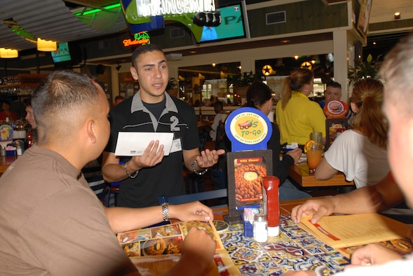 "Airman 1st Class Joshua Garcia, 18th Security Forces Squadron, talks to customers at Chili's on Kadena Air Base, Japan, about giving donations to Special Olympics during the ""Tip-a-Cop"" fundraiser June 2. Airman Garcia was one of 42 military police members from all branches of service to volunteer for the event that raised more than 2,500 dollars.
