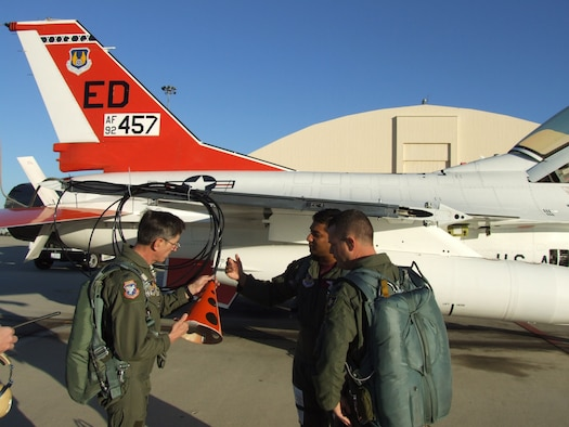 Col. Andre Gerner (left), U.S. Air Force Test Pilot School commandant, checks out an F-16B trailing cone assembly, as Maj. Swami Iyer (center), test pilot, and Lt. Col. Dean Ward (right), TPS operations officer, look on. (Courtesy photo)