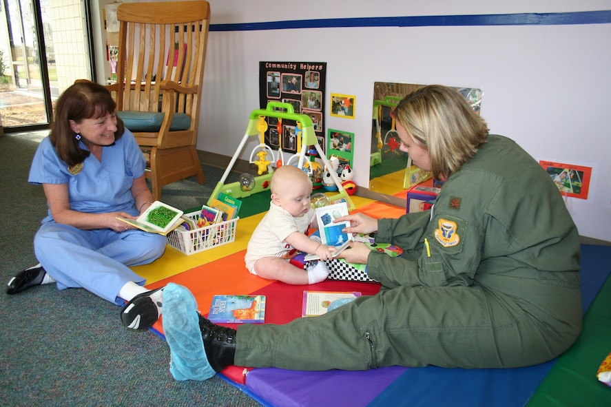 Maj. Jennifer Avery, 509th Operational Support Squadron, with the help of caregiver Shirley Witt, shows her son Avery  a book to teach him the basics of reading.