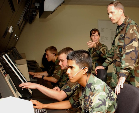 From left, Airmen Basic Devon Cross, Joshua Saville and Arturo Herrera train at air traffic control radar simulators as Master Sgt. Lori Derr, instructor, talks to the 334th Training Squadron's new commander, Lt. Col. Douglas Chowning, about the squadron's training mission. Colonel Chowning took command from Lt. Col. Richard Miller May 23.  He came to Keesler from Hickam Air Force Base, Hawaii, where he was deputy chief for the air operations division at Pacific Air Force's directorate of air, space and information operations, plans and requirements.  A Missouri native and Air Force Academy graduate, Colonel Chowning is a command pilot with more than 3,200 flying hours.  He's served in squadron and major command positions in Europe, Central and South America and the Pacific.  Colonel Miller is headed to Royal Air Force Croughton, England, to command the 422nd Air Base Group.  (U. S. Air Force photo by Kemberly Groue)