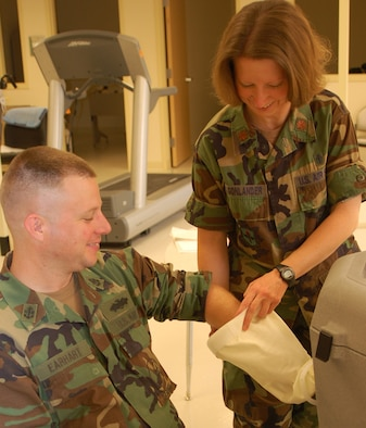 Maj. Susan Wagonlander,  81st Surgical Operations Squadron occupational therapist, helps Navy Chief Electrician Phil Earhart, Naval Construction Battalion Center-Gulfport, put his lower arm into a fluido-therapy machine.  The heated dry whirlpool device is used to help patients regain range of motion.  Outpatient occupational therapy services for referral patients are in Room BC300, Keesler Medical Cen-ter.  Hours are 7 a.m. to noon and 1-5 p.m. Monday-Thursday and 7 a.m. to noon and 1-4 p.m. working Fridays. (U. S. Air Force photo by Steve Pivnick)