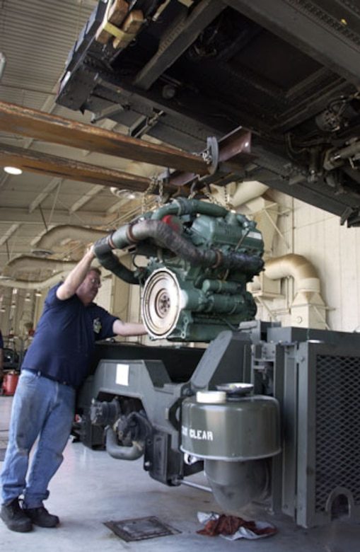 Tom Gillis, a contractor with Satellite Services, Inc., helps remove the engine on a Tunner 60K loader before replacing it with a new $40,000 engine. This is the first time since March has owned their Tunners that this procedure has ever taken place. It is a Detroit Diesel, 6 cylinders 350 HP, 5.3 Liter Engine weighing roughly 1700 lbs. Gillis, Fred Caluya, also a contractor, and Tech Sgt. Chan Sivon, an SSI trained reservist with the 452nd Logistics Readiness Squadron, worked for over a week to ensure the Tunner was operable and ready to work again and, in the process, gained some valuable training. (U.S. Air Force photo by Amy Abbott)