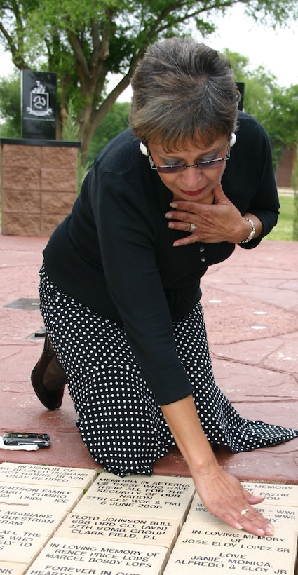 Janie Lopez mourns after placing the brick dedicated to her husband, Jose Lopez, who died last year. June 6 marked the one-year anniversary of the dedication of the memorial at Cannon Air Force Base. (U.S. Air Force photo by Airman Elliott Sprehe)