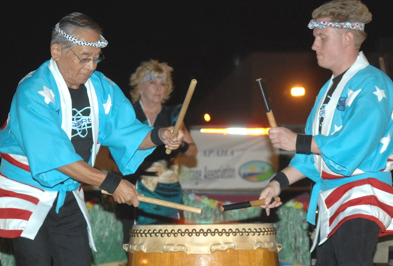 Kenji Azeka (left) and Nick Ballinger, both members of Suzuyuki-Kai MoGan Daiko, perform Taiko drumming to represent the culture of Japan during the Asian/Pacific American Heritage Luau at Bama Park here June 1. (U.S. Air Force photo/Senior Airman Christina D. Ponte)