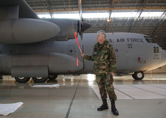 Col. Michael Riddle inspects a propeller of a C-130 Hercules. Colonel Riddle will relinquish command to Col. Gerald Frisbee at 9 a.m. June 14 at the Yokota Enlisted Club. (Photo by Senior Airman Veronica Pierce 070207-F-3177P-001)