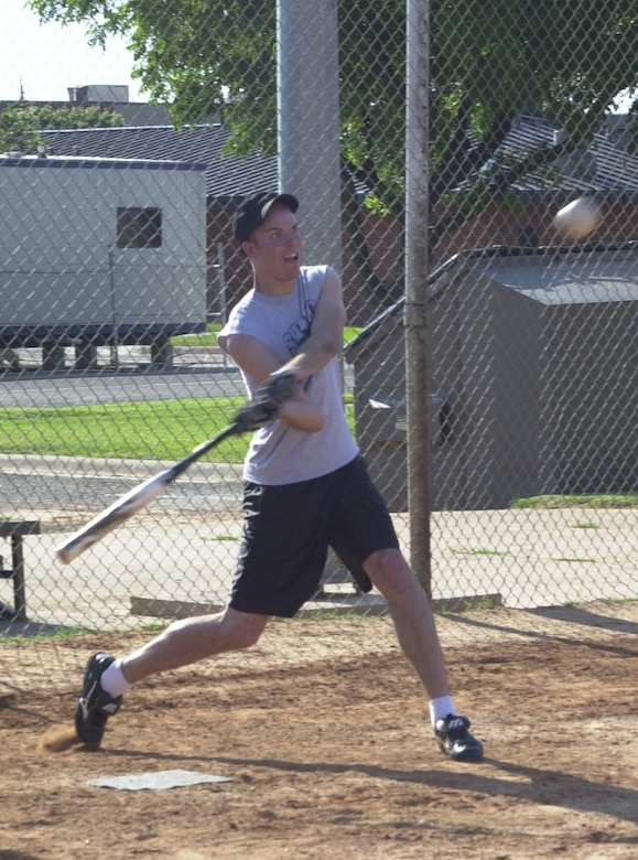 Keeping his eyes on the ball is 316th Training Squadron Beta Sharks outfielder Chris Okuley, taking a swing during a practice game Tuesday at Softball Field 1. The official intramural softball games were cancelled due to weather concerns, but that didn't keep some players from playing ball. Members of the 316th Training Squadron Beta Sharks and the 17th Mission Support Group Junk Yard Doggs mixed their player rosters and decided to play a friendly exhibition game. (U.S. Air Force photo by Airman 1st Class Luis Loza Gutierrez)