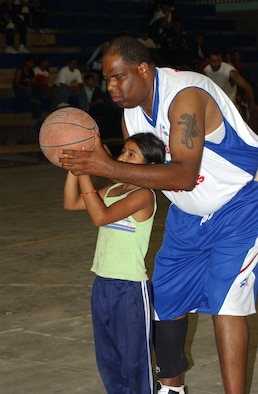 Army Sgt. Alonzo Lunsford, a member of the Soto Cano Air Base basketball team, the Comayagua Iguanas, shows the proper shooting technique to young Honduran girl June1 in Siguatepeque, Honduras. Sergeant Lunsford is a player and coach for the base team. The team receives invitations to travel and play local Honduran teams. Sgt. Lunsford says the games offer a key avenue to bridge the cultural gaps between Americans and Hondurans. U.S. Air Force photo by Senior Airman Shaun Emery.