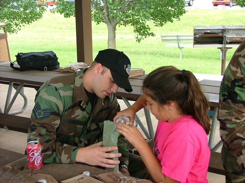 During the 3rd Herd Pen Pal visit the week of May 28, 31st Combat Communications Squadron member Staff Sgt. Benjamin Stolz helps his pen pal heat up her Meals Ready to Eat.