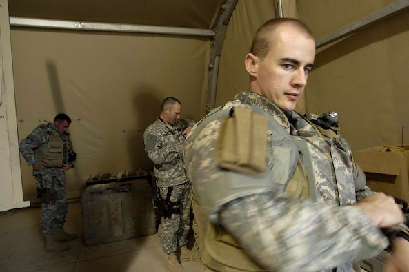 Senior Airman William Newman dons his protective equipment prior to a mission April 3 at Balad Air Base, Iraq. Airman Newman was deployed from Hickam Air Force Base, Hawaii and was killed June 7 from an improvised explosive device. In background are Staff Sgt. Charles Warner and Staff Sgt. Tom Pilla, both deployed from Ramstein Air Base, Germany. Airman Newman was assigned to the 332nd Expeditionary Civil Engineer Squadron's Explosive Ordnance Disposal Flight with Airmen Warner and Pilla.  (U.S. Air Force photo/Airman 1st Class Nathan Doza)