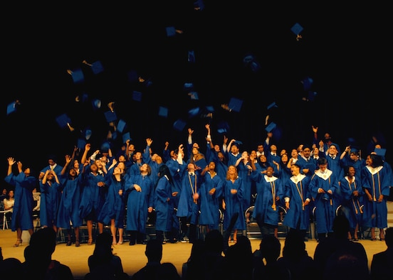 Seniors from Yokota High School, Japan, celebrate by tossing their graduation caps in the air on Jun. 7; at the Fussa City Community Center.