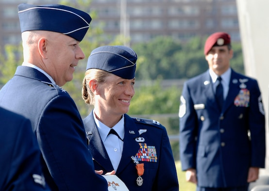 Air Force Chief of Staff Gen. T. Michael Moseley presents Capt. Allison Black of the 1st Special Operations Squadron, with the Air Force Combat Action Medal as Senior Master Sgt. Ramon Colon-Lopez stands at attention. Six Airmen received the medal in a ceremony June 12 at the Air Force Memorial in Arlington, Va. (U.S. Air Force photo/Staff Sgt. Brian Ferguson)