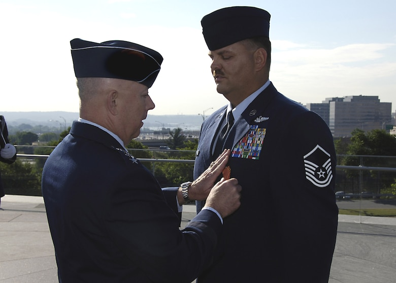 Air Force Chief of Staff Gen. T. Michael Moseley awards an Air Force Combat Action Medal to Master Sgt. Byron Allen at the Air Force Memorial June 12 in Arlington, Va., June 12. Sergeant Allen was one of six Airmen to receive the medal, awarded to Airmen who have been directly in harm's way, engaging enemy forces. Sergeant Allen was serving as an MH-53 aerial gunner was conducting a combat resupply mission when his aircraft came under enemy fire. Sergeant Allen is from the 1st Special Operations Group, Hurlburt Field, Fla. (U.S. Air Force photo/Donna Parry)