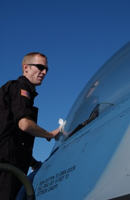 EIELSON AIR FORCE BASE, Alaska --  Senior Airman Jed Winkelman, 64th Aggressor Squadron, Nellis Air Force Base, Nev., cleans the canopy of an F-16 June 8. Airman Winkelman is one of many crew chiefs from around the Air Force who came to participate in Red Flag 07-02, which runs through June 15.  (U.S. Air Force photo by Airman 1st Class Christopher Griffin)