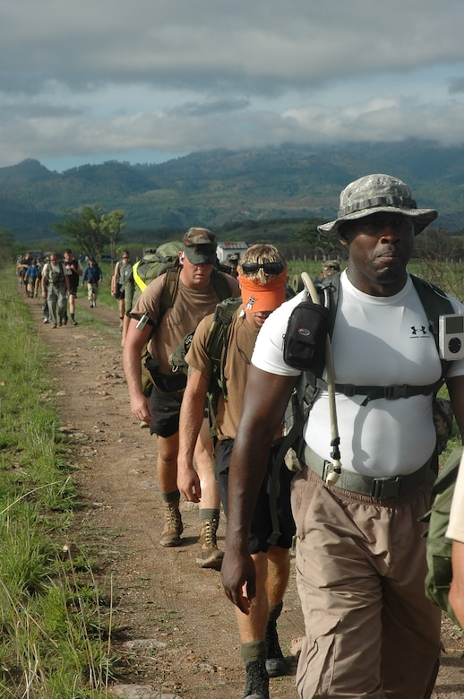 """Army Staff Sgt. Shelley Croker leads a group of marchers across the comyagua valley on the second day of the two-day march from Tamara, Honduras. The march officially named """"The Iguana Challenge"""" was a command directed volunteer march for members of Joint Task Force-Bravo and Honduran Military members. The 30-mile march took particpants over the mountains surrouding Soto Cano Air Base."""